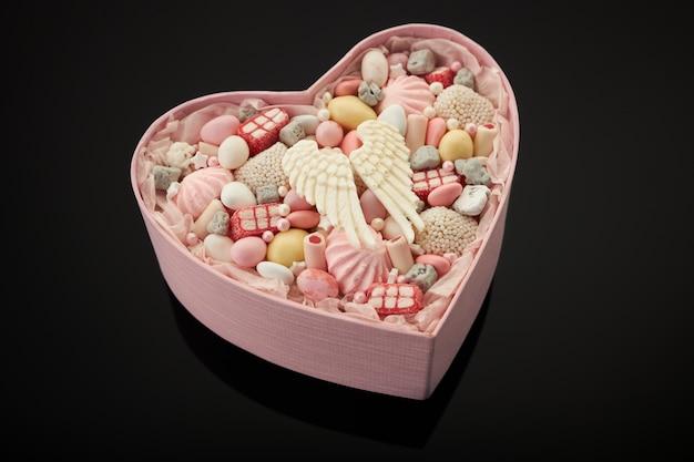Scatola rosa a forma di cuore piena di caramelle e marshmallow diversi