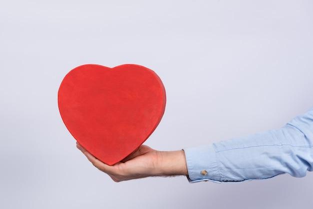 Scatola rossa a forma di cuore in mano, sfondo bianco. regalo per l'amato. presente per san valentino
