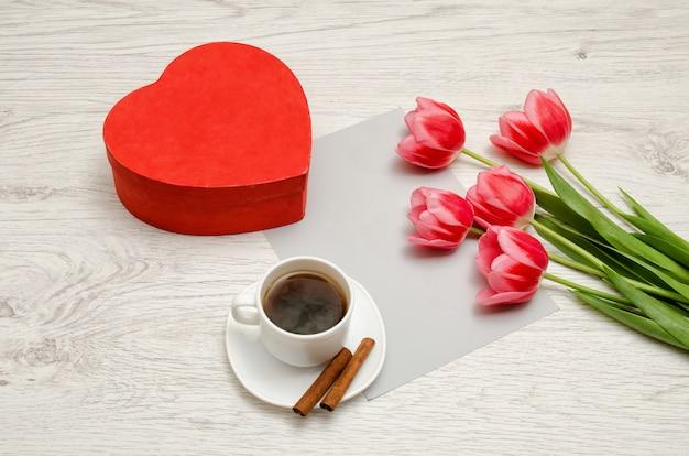 Scatola rossa a forma di cuore, tulipani rosa, foglio grigio e una tazza di caffè. tavolo luminoso