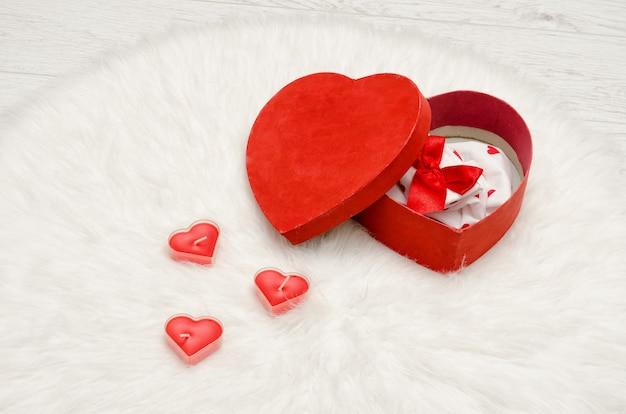 Scatola rossa aperta con lino rosso e bianco a forma di cuore su una pelliccia bianca. candele a forma di cuore