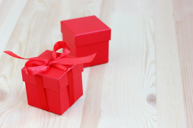 Scatola rossa con fiocco di nastro sulla tavola di legno