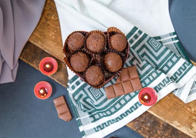 Scatola rossa di cioccolatini, barretta di cioccolato al latte e candele fiammeggianti sulla tovaglia