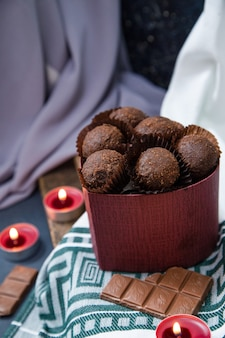 Scatola rossa di cioccolatini, barretta di latte e candele fiammeggianti sulla tovaglia