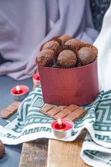 Scatola rossa di cioccolatini, latteo e candele fiammeggianti su un pezzo di legno