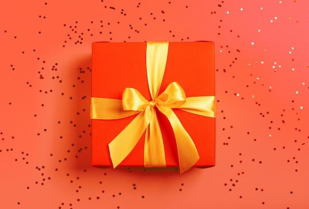 Scatola rossa legata con un nastro d'oro. il nastro è legato su una scatola sotto forma di un bellissimo arco.
