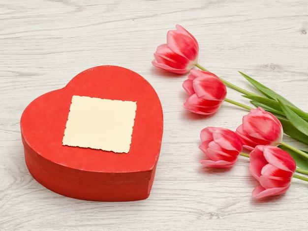 Scatola rossa nella carta pulita di forma del cuore, tulipani rosa su un fondo di legno leggero. vista dall'alto, spazio per il testo