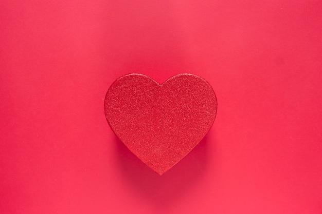 Scatola rossa scintillante a forma di cuore isolata su fondo rosso. il contenitore di regalo di san valentino con lo spazio della copia, deride su.