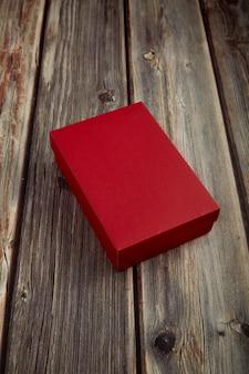 Scatola rossa vuota su legno marrone brillante