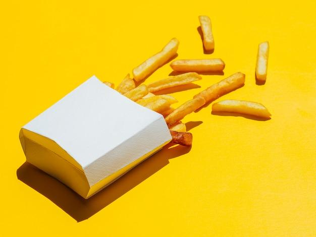 Scatola rovesciata di patate fritte su fondo giallo