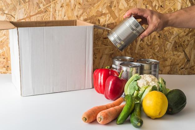 Scatola vuota con vestiti e cibo vicino alla scatola sul tavolo bianco
