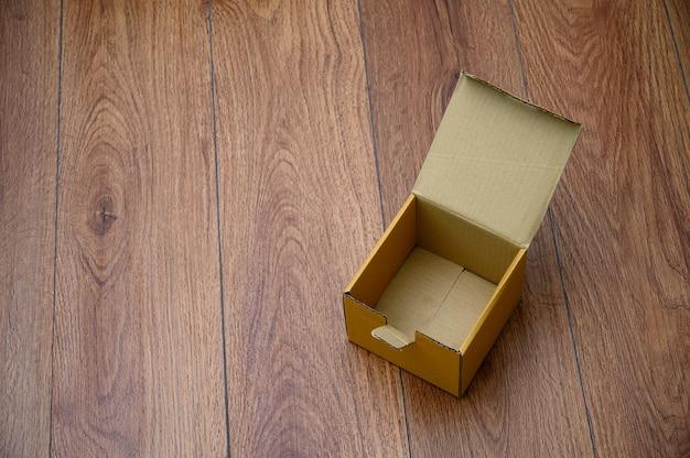 Scatola vuota scatola di cartone aperta sulla superficie in legno con spazio vuoto top disposizione piatta