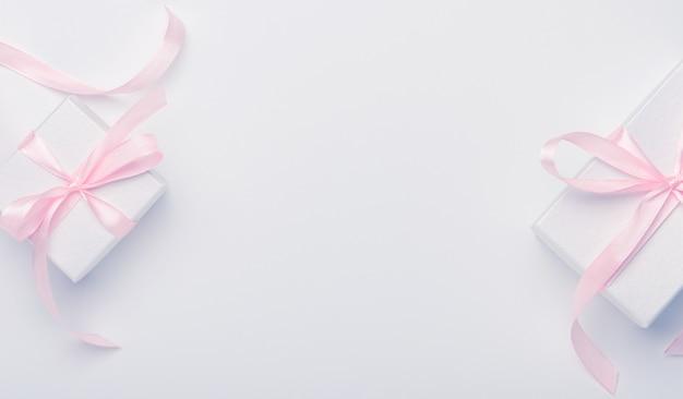 Scatole bianche con il nastro rosa su bianco.