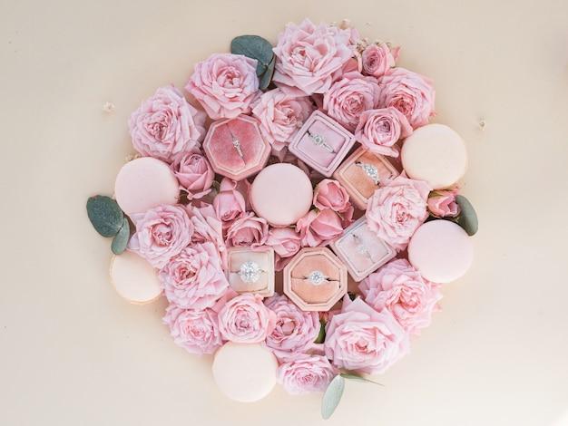 Scatole con anelli si trovano tra i fiori su un tavolo
