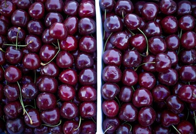 Scatole con ciliegie rosse fresche, bancone del venditore di frutta e verdura, mercato agricolo