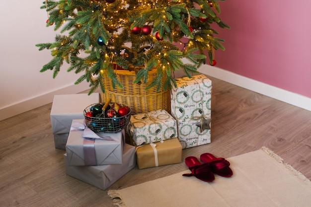 Scatole con regali di natale sono sull'albero con le luci