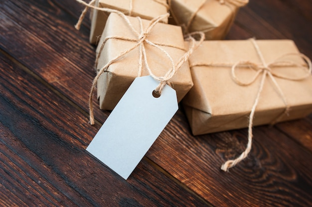 Scatole del modello per i regali della carta kraft e le etichette del regalo su una superficie di legno