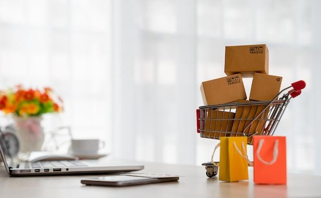 Scatole del pacchetto del prodotto nel carrello e laptop sulla scrivania