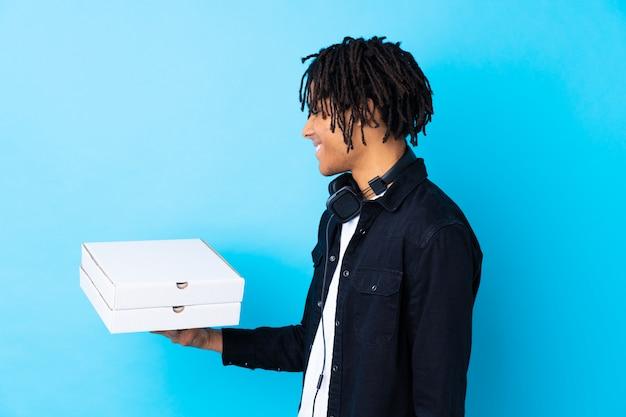 Scatole della pizza della tenuta del giovane sopra la parete isolata