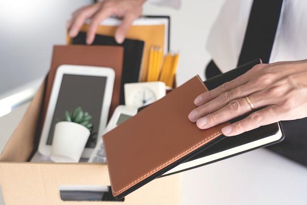 Scatole della stretta dell'uomo d'affari compreso la pianta da vaso e documenti
