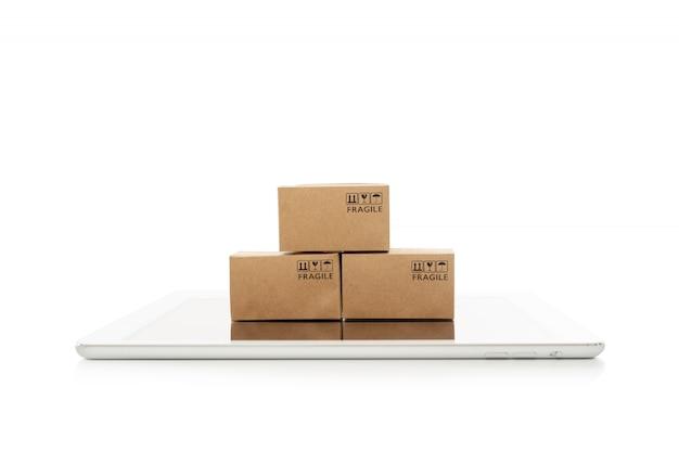 Scatole di carta con la compressa su fondo bianco, sullo shopping online o sul concetto di ecommmerce
