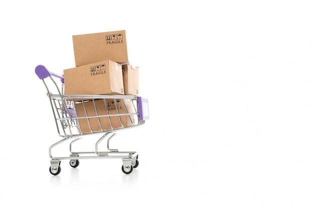Scatole di carta in un carrello su fondo bianco, sullo shopping online o sul concetto di ecommmerce