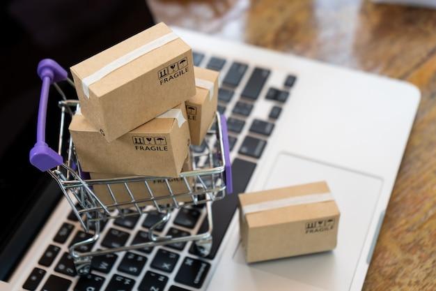 Scatole di carta in un carrello su un computer portatile, concetto online di acquisto facile