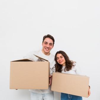 Scatole di cartone di trasporto delle giovani coppie felici disponibili che esaminano macchina fotografica isolata su fondo bianco