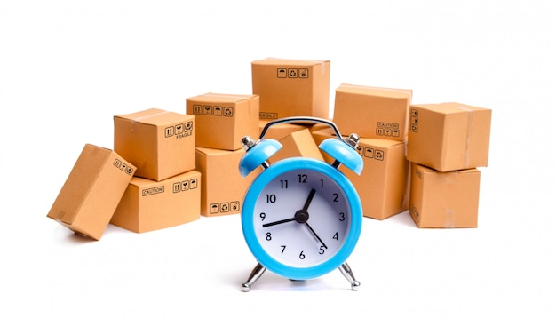 Scatole di cartone e orologio su sfondo bianco.