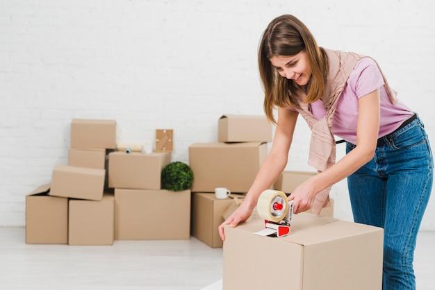 Scatole di cartone felici dell'imballaggio della giovane donna facendo uso del distributore del nastro