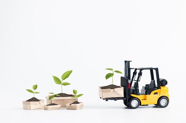 Scatole di cartone miniatura di caricamento del modello del carrello elevatore a forcale che contengono plantula isolata su fondo bianco.