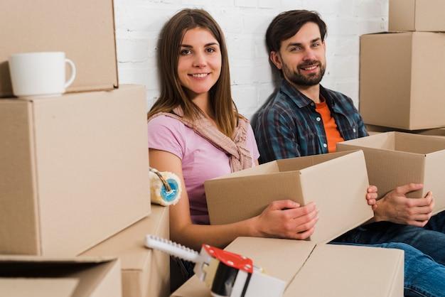 Scatole di cartone sorridenti della tenuta delle giovani coppie che si rilassano in nuova casa