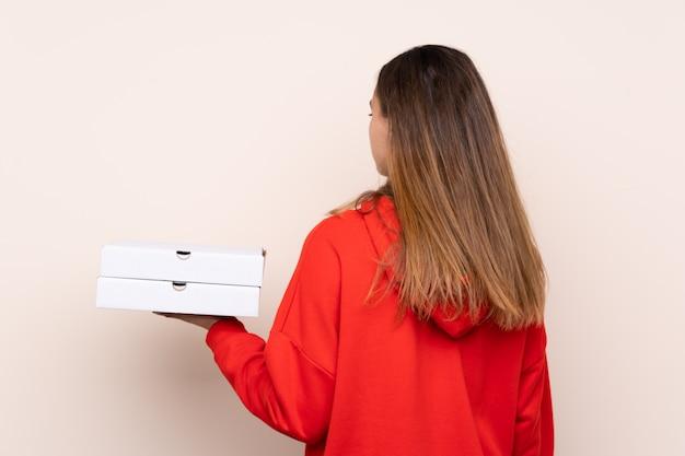 Scatole di pizza di cattura della ragazza sopra la parete isolata