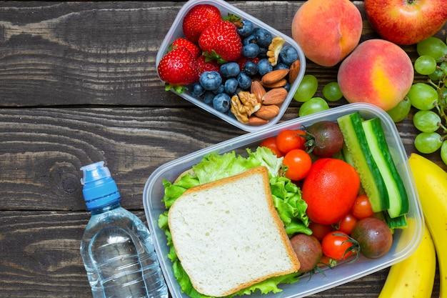 Scatole di pranzo di scuola con sandwich, frutta, verdura e bottiglia d'acqua e copia spazio