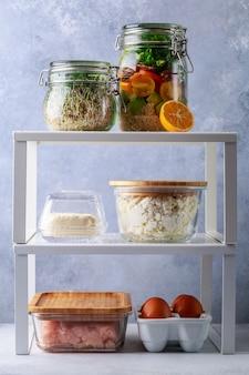 Scatole di vetro e lattine con decantazione del concetto di stoccaggio frigorifero per alimenti freschi