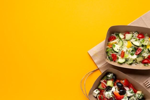 Scatole piane di disposizione con insalata su fondo giallo