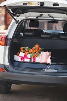Scatole presenti in macchina. regali nel bagagliaio dell'automobile. mazzo di tulipani nel bagagliaio.