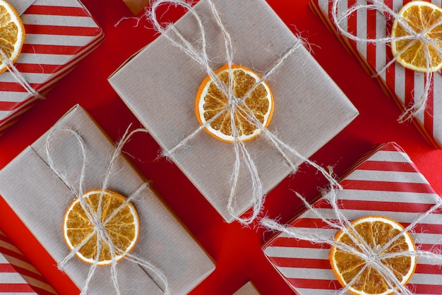 Scatole regalo a strisce rosse e naturali, decorate con arancia essiccata. disposizione obliqua delle scatole una accanto all'altra.