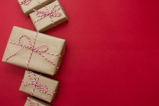 Scatole regalo artigianale su sfondo rosso. natale mock up con spazio di copia.