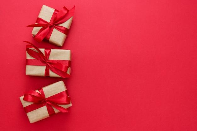 Scatole regalo avvolte con carta kraft e fiocco rosso isolato su sfondo rosso. piatto astratto laici.