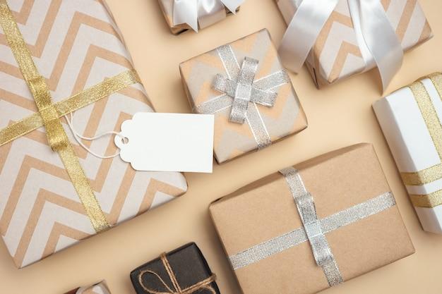 Scatole regalo avvolte in carta kraft con nastro bianco, argento e dorato e fiocco sul tavolo beige pastello. etichetta regalo vuota. concetto attuale di festa. vista dall'alto.
