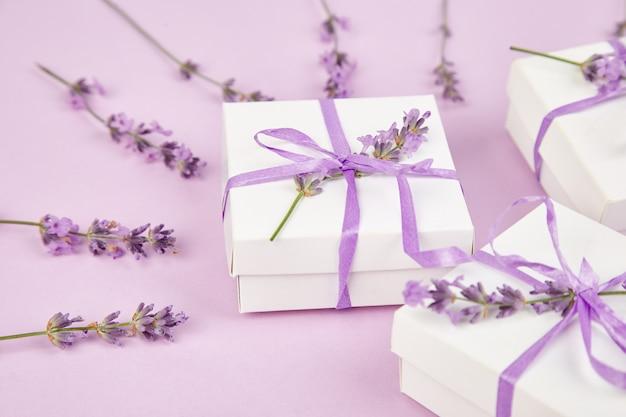 Scatole regalo bianche con nastro viola e fiori di lavanda