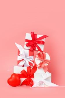 Scatole regalo bianco con nastri di raso rosso su uno sfondo rosa. regali festivi per san valentino, giornata internazionale della donna, matrimonio o fidanzamento.