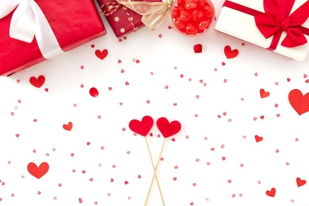 Scatole regalo, caramelle e forme cuore rosso su carta bianca