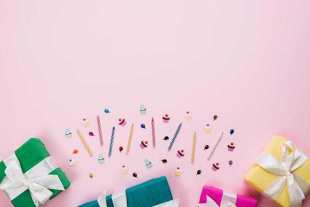Scatole regalo colorate avvolte; candele e adesivi di compleanno su sfondo rosa