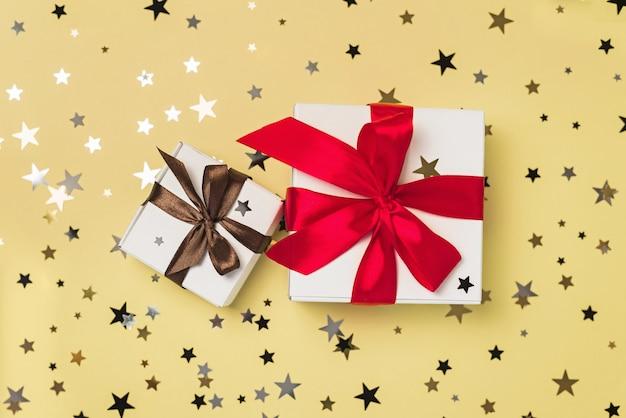 Scatole regalo con nastri rossi e marroni sul tavolo giallo con coriandoli di stelle glitter.