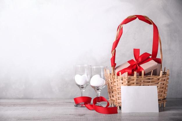 Scatole regalo con nastri rossi su un cesto, due cuori bianchi in bicchieri di vino e lettera d'amore in bianco