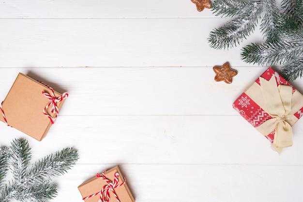 Scatole regalo con rami di abete di neve e biscotti stelle su un fondo di legno bianco. biglietto natalizio. copriletto piatto