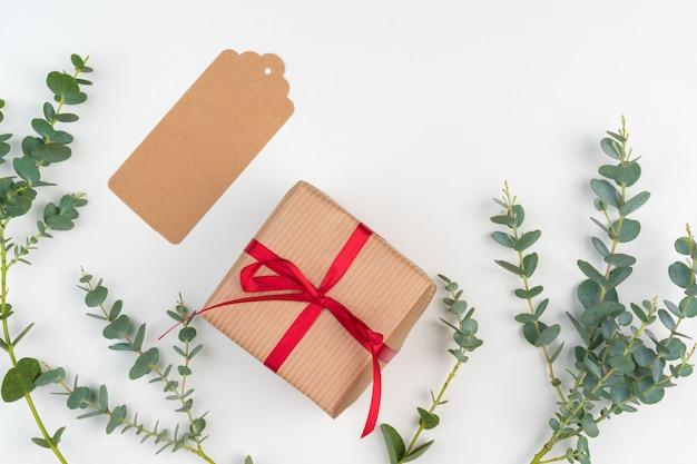 Scatole regalo confezionate in carta artigianale con decorazioni semplici di rami di piante verdi