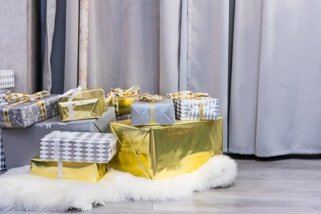 Scatole regalo contro un bokeh di sfondo di luci di partito scintillanti. regalo di capodanno di lusso.