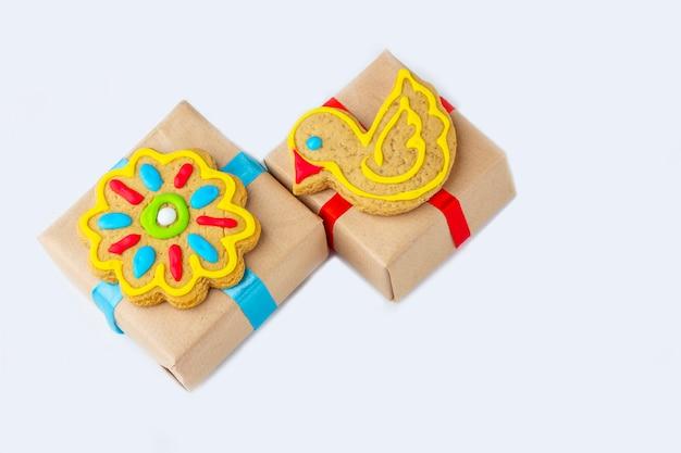 Scatole regalo decorate con biscotti di panpepato dipinti fatti in casa isolati su uno sfondo grigio. concetto di regalo dolce di natale, capodanno o pasqua. primo piano divertente cibo dolce.